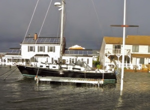 Eisberg's sailboat became a lifeboat when the floodwaters of Barnegat Bay forced him from his house. The morning after Sandy, the yard and bulkhead behind his Brick Township house were still submerged. (Photo courtesy Jon Eisberg.)