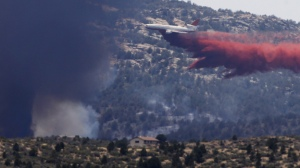 An aerial tanker drops fire retardant on a wildfire threatening homes near Yarnell, Ariz., on July 1. An elite crew of firefighters was overtaken by the out-of-control blaze on June 30, killing 19 members as they tried to protect themselves from the flames under fire-resistant shields. (Photo by Chris Carlson/AP)