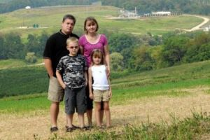 The Hallowich family in 2010, standing on a hillside near their home to illustrate the proximity of several gas wells around their property. (Photo by Pam Panchak/Post-Gazette)
