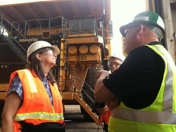Mining Country Fellow Christy George talks with Cliffs Natural Resources' Bill Hemmila in front of a mega truck. (Photo IJNR)