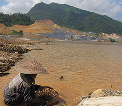 A villager washes in the Mekong, with Xayaburi Dam construction in background. (Photo courtesy International Rivers)