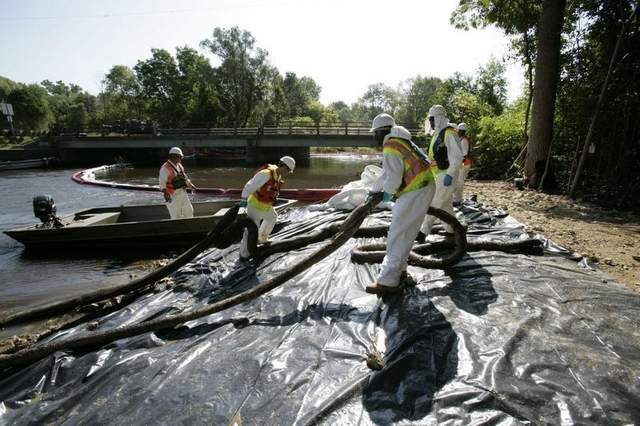 Workers pull oil-soaked absorbing booms from the Kalamazoo River near Marshall on Friday, Aug. 6, 2010. (Photo by Patricia Beck/Detroit Free Press)